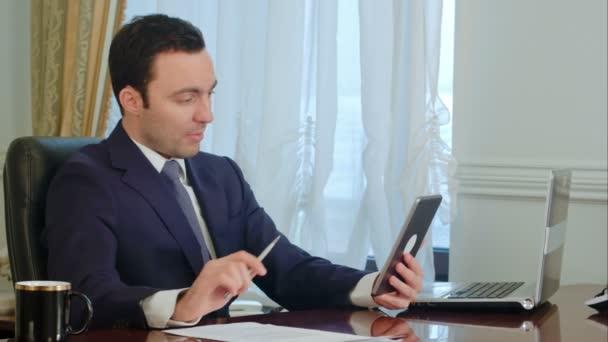 Gut aussehend Kaufmann hat treffen auf Tablet mit Unterlagen auf dem Schreibtisch im Büro