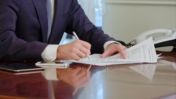 Mano delluomo firma un documento di carta con una penna. Firma è falso.