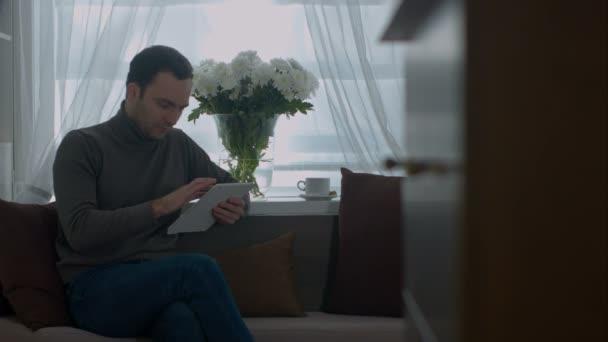 Junger Mann Suche Internet mit Tablet-PC auf sofa