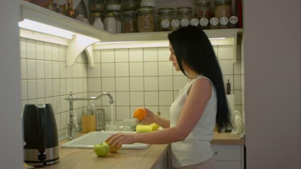 Žena Mladá hospodyně, mytí čerstvé ovoce v kuchyni pod proudem vody, příprava ovocný salát