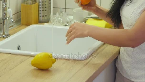 Frauenhände waschen Orange im Wasser