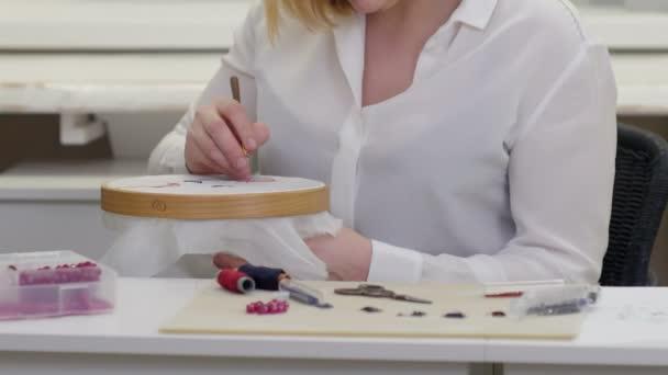 Žena rukou vyšívání luneville hákem na hedvábí