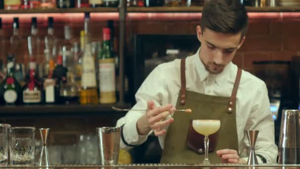 Bartender making and decorating cocktail to a visitor