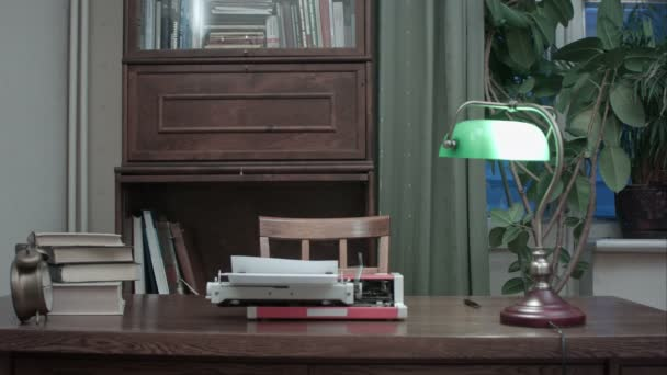 Retro typewriter with books and green lamp on the table
