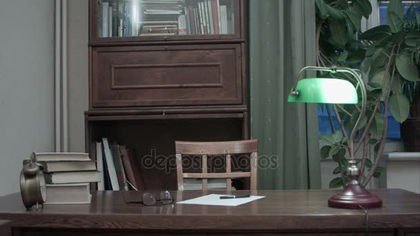Writer desk with books, paper, glasses and green lamp turned on