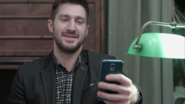 Mladý muž sedí u stolu a pořizování selfie na svém telefonu a jeho odesláním
