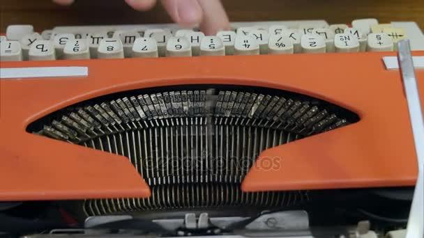 Muži prsty psaní na vintage červené psaní stroj