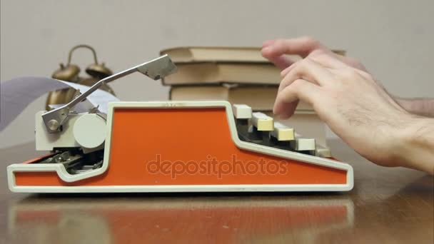 Mans hands typing on a red retro typewriter on a table with books