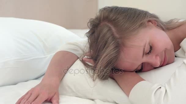 Uvolněná mladá blonďatá dívka spí na bílé posteli, doma nebo v hotelovém pokoji