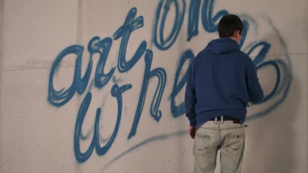 Young man drawing graffiti on a wall with a spray can