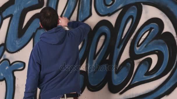 jonge stedelijke schilder tekenen van graffiti op de muur