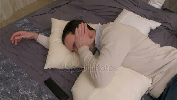Unavený mladý muž leží na posteli a usne po tvrdé pracovní den