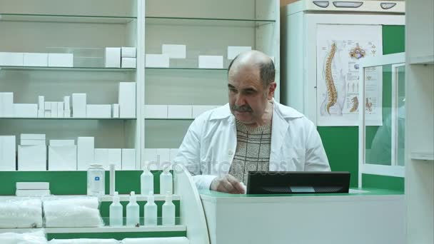 Senior male pharmacist with mustache posing at the drugstore, working with medicine and computer