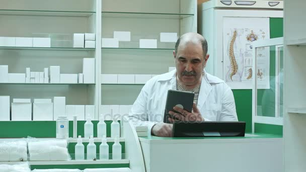 Senior pharmacist with mustache working on tablet pc checking medicine in pharmacy