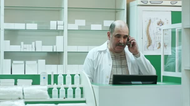 Pharmacist talk with client using mobile phone in pharmacy