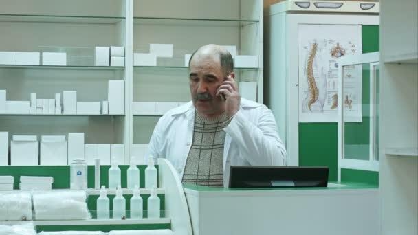 Lékárník konzultační zákazníka prostřednictvím mobilního telefonu v drogerii