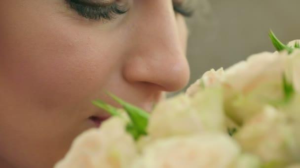 Mladé ženy vonící růže a usmívá se