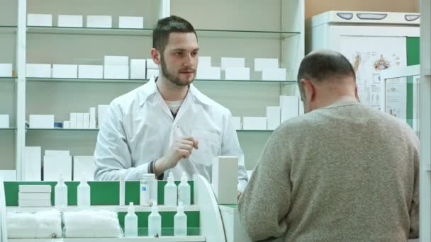 Young pharmacist giving drug to senior man customer and taking payment in dollars at drugstore