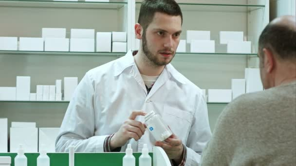 Young pharmacist advicing pills senior man customer at drugstore