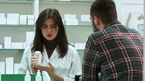 Young female pharmacist suggesting medical drug to male buyer in pharmacy drugstore