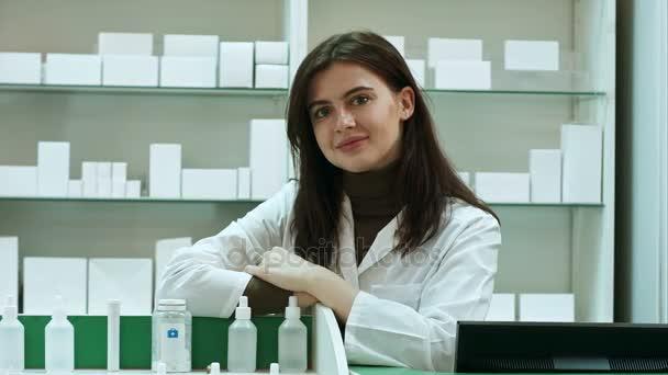 Lächelnd, glücklich selbstbewusste junge Frau Apotheker stützte sich auf einen Schreibtisch in der Apotheke geben der Kamera ein schöne warme freundliche Lächeln