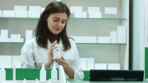 A cheerful young woman pharmacist with a bottle of drugs standing in pharmacy drugstore looking at camera