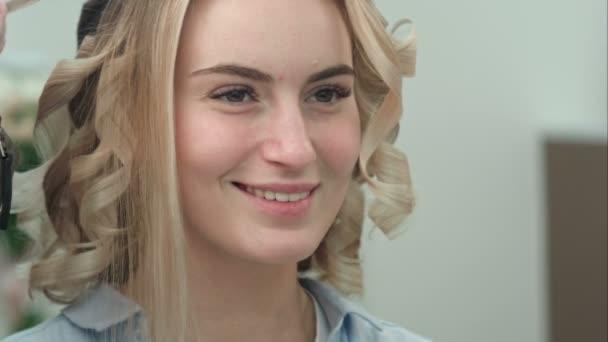 Odraz usměvavá mladá žena s blond vlasy salon zrcadla s vlasy stylizované