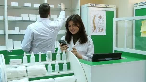 Ženské lékárníka jak pozitivní pomocí smartphone, mluvil s její kolegyně