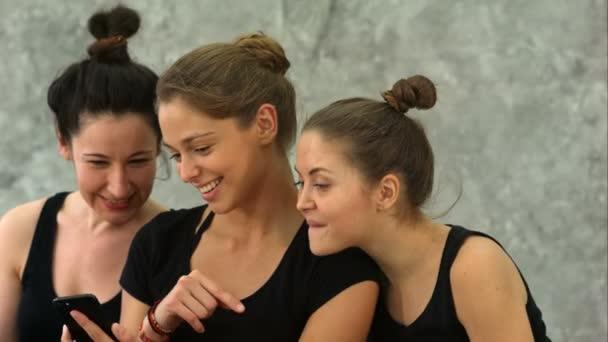 Tři mladé ženy procházení Internetu pomocí smartphone po cvičení v jógy