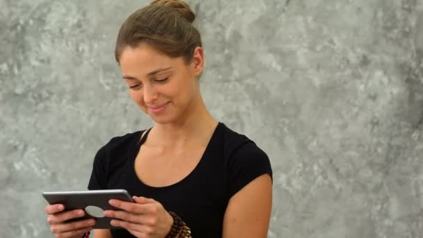 Smiling cute young woman using tablet in yoga studio