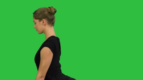 Side view portrait of beautiful young woman doing yoga or pilates exercise. One Legged King Pigeon pose, Eka Pada Rajakapotasana on a Green Screen, Chroma Key