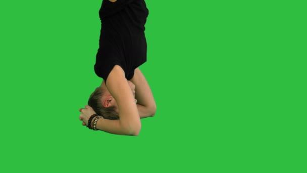 Mädchen beim Yoga asana upavishtha konasana shirshasana, gebundene Winkel-Pose im Kopfstand auf einem grünen Bildschirm, Chroma-Taste