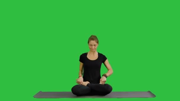sportlich attraktive Frau praktiziert Yoga, sitzt in voller Lotus-Übung, siddhasana Pose, arbeitet auf einem grünen Bildschirm, Chroma-Taste