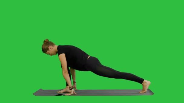 schöne junge Frau in schwarzer Sportbekleidung beim Training, Yoga oder Pilates auf einem grünen Bildschirm, Chroma-Taste