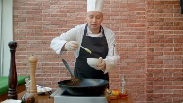 gutaussehender Koch bereitet Pfanne mit Teig zu und spricht in die Kamera