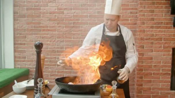 Šéfkuchař připravuje mořské plody v pánvi s alkoholem v ohromném plameni