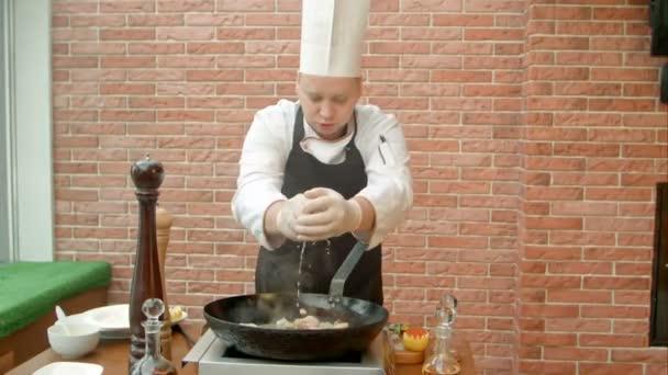 Chef fügt Zitronensaft in Pfanne mit gebratenen Meeresfrüchten hinzu