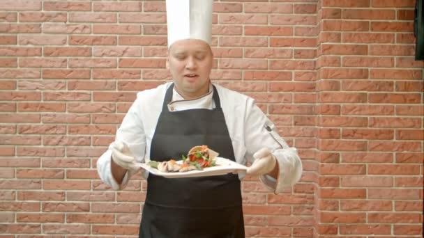freundliche Köchin in Uniform präsentiert einen Teller mit Fischsalat und spricht in die Kamera