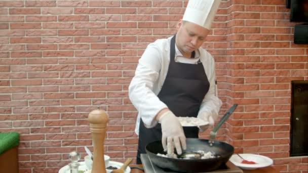 Koch bringt frische Meeresfrüchte in die Pfanne