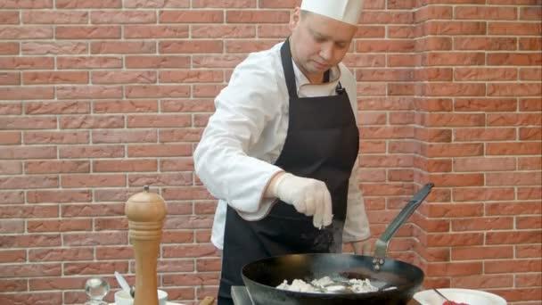 Szakács elhelyezés cirmos a serpenyőben a főzés a tenger gyümölcsei