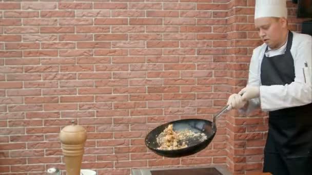 Koch bereitet Paella mit Meeresfrüchten zu, mixt das Gericht mit fliegender Pfanne