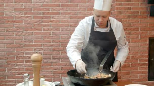Koch probiert das Gericht und gibt Salz in die Pfanne