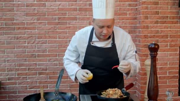 Hezký mužský kuchař oblečený v bílé uniformě zdobí paella a při pohledu na fotoaparát s úsměvem