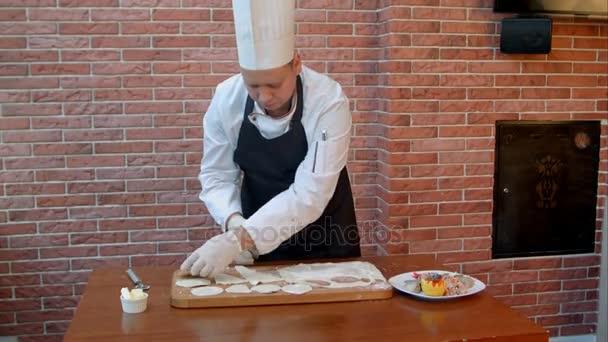 Kuchař vykrojte kolečka ze syrové těsto cookie vrácena šev na dřevěném prkénku