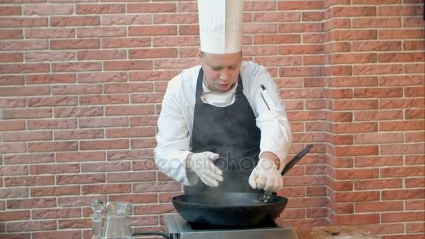 Kuchař v restauraci vaření smažené knedlíky s mořskými plody v pánvi, mačkání citronu