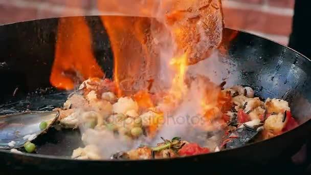 Příprava mořských plodů ve velkém plameni v pánvi