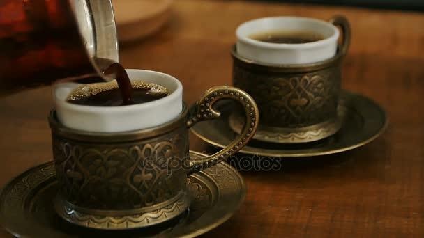 zwei Tassen schwarzen Kaffee aus einem Türken gegossen