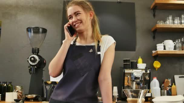 Junge Frau telefoniert mit Handy am Arbeitsplatz