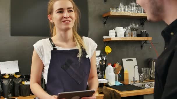 Porträt einer hinreißenden Barista, die mit einem Tablet-Computer die Bestellung einer Kundin entgegennimmt und lächelt