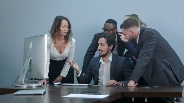 Group of multiracial business people around the conference table looking at laptop computer and talking to one another